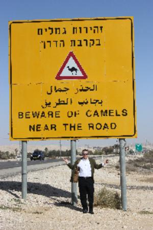 "A person standing in the desert underneath a yellow sign in Arabic and English that says ""Beware of Camels near the road"""