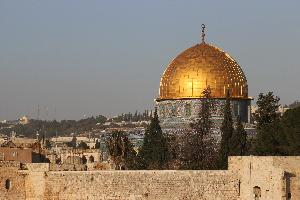 A dome covered in gold at the top with mosaic designs on the bottom. There is a blue sky and other buildings behind it.