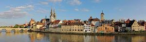 A panorama of the city of regensburg from the river including a brick brdieg, a cathedral, old style houses and a clock tower.