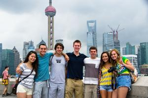 Group of students in Shanghai, with city skyline behind them.
