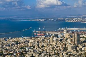 a view of the city of Haifa with several buildings, a few skyscrapers, and a view of the ocean.