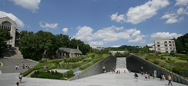 A photo of the university and a descending slope into an underground classroom