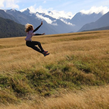 A mountain view background with a student jumping in the fields