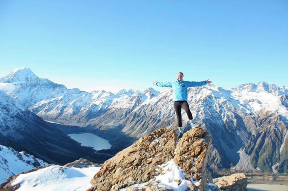 a student standing on the tip of a mountain with more snowy mountains in the background